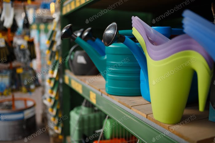 Watering cans on the shelf, shop for floristry