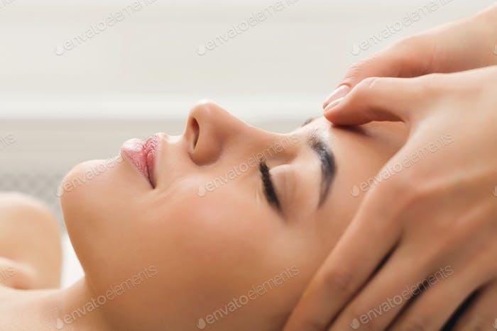 Woman getting professional facial massage at beauty salon