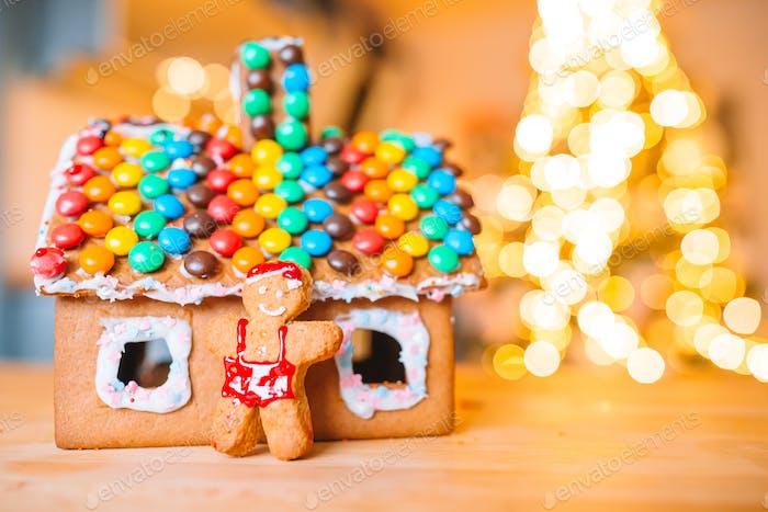 Hausgemachtes Weihnachts-Lebkuchenhaus auf einem Tisch. Weihnachtsbaumlichter im Hintergrund