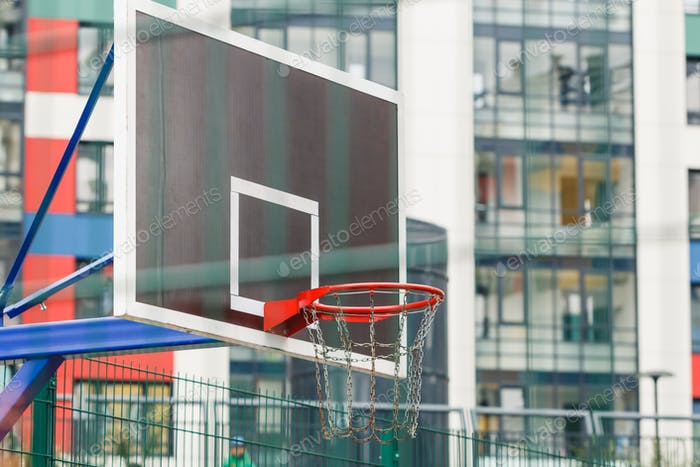 Basketball ring on a closed court in the courtyard of a multi-storey building.