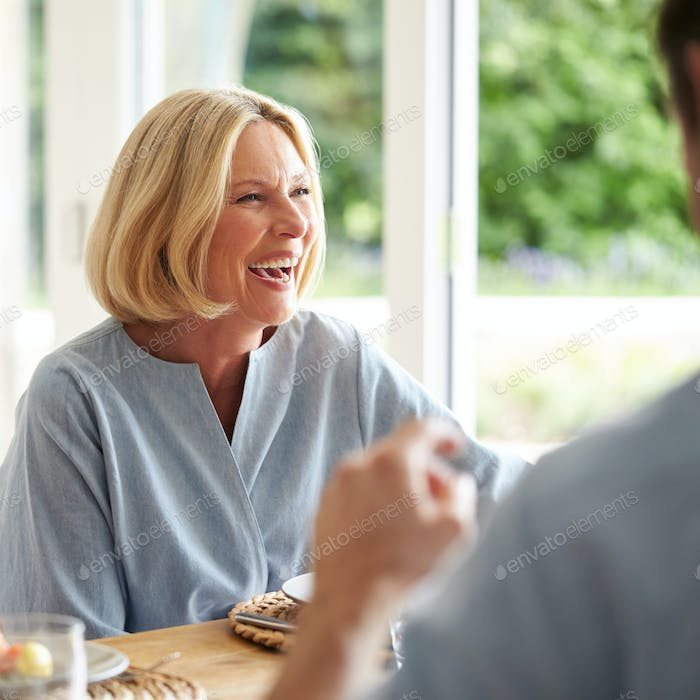 Family With Senior Mother And Adult Son Eating Brunch Around Table At Home Together