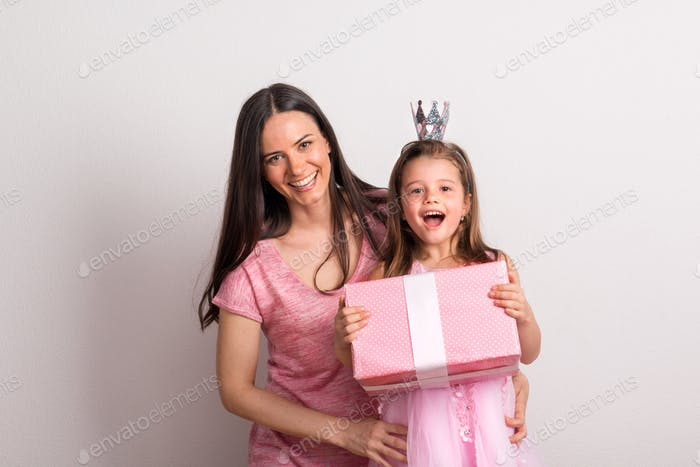 A small girl with crown headband and her mother holding a present in a studio.