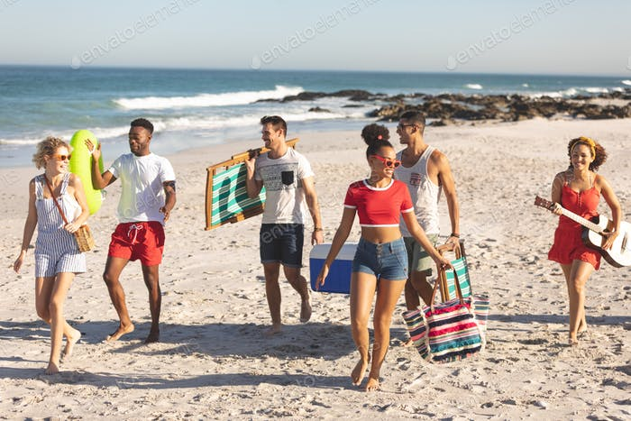 Front view of group of happy diverse friends walking together on the beach