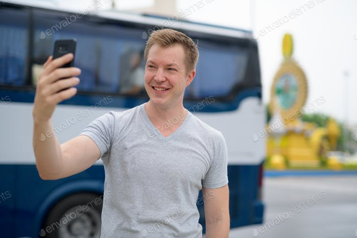 Young happy tourist man taking selfie against Ratchadamnoen street in Bangkok