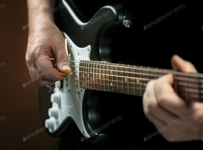 man's hands playing on electric guitar
