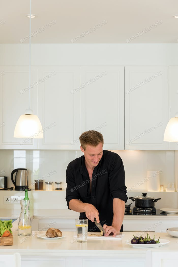 Couple cooking on a white island kitchen at home