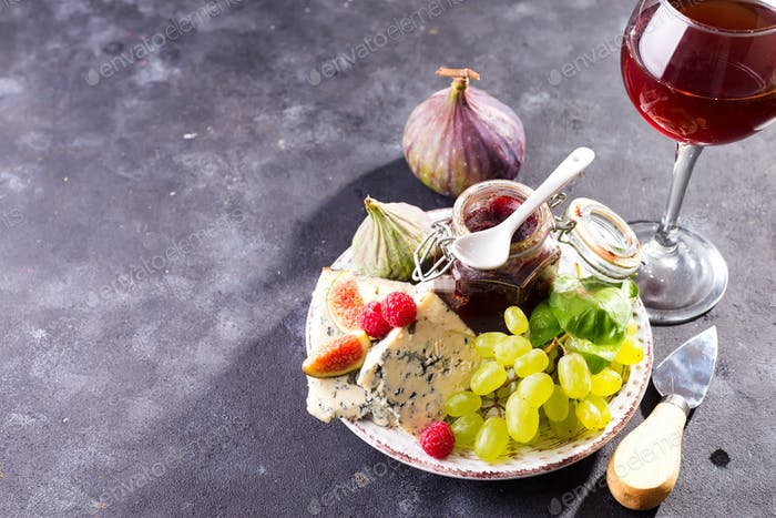 Assortment of cheese, berries and grapes with red wine in glasses. on stone background. Copy space