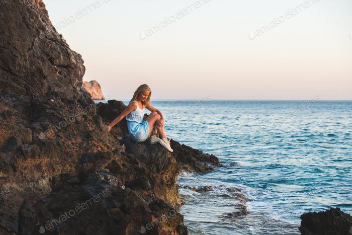 Young blond woman tourist in blue dress sitting