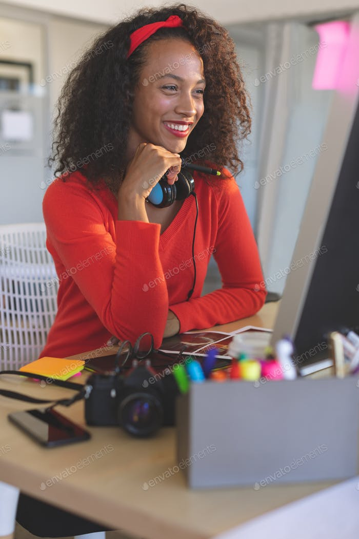 Young female graphic designer working on desktop pc at desk in a modern office. She is smiling