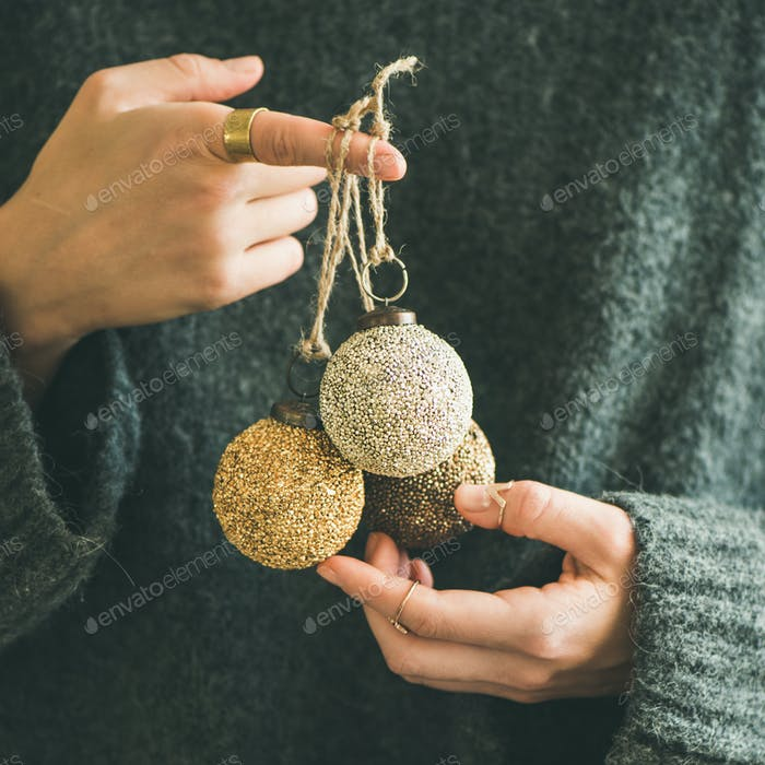 Woman in grey sweater holding decorative golden balls