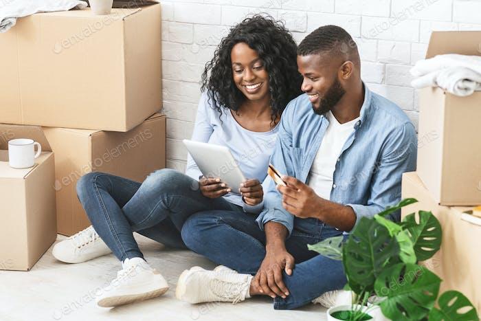 Fröhliches Paar Kauf neuer Möbel online, mit digitalem Tablet