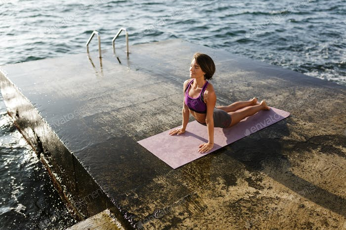 Beautiful lady in sporty top and shorts practicing yoga with sea on background