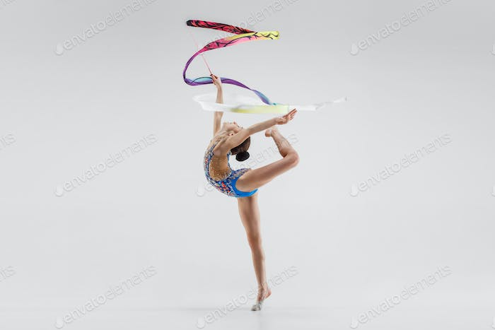 The portrait of beautiful young brunette woman gymnast training calilisthenics exercise with ribbon