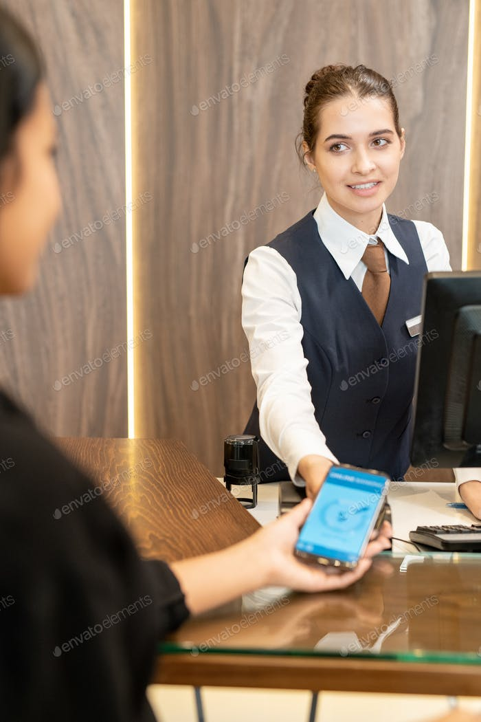 Young hotel receptionist looking at female client