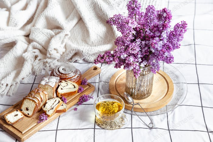 Breakfast or brunch in bed with pastries and flowers.