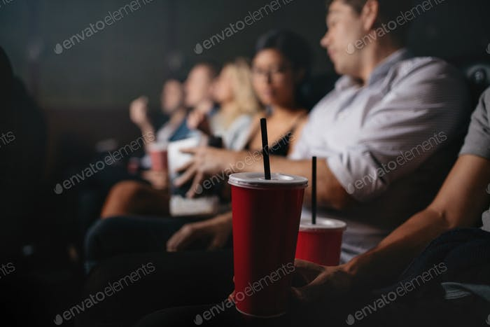 People with soft drinks in watching movie