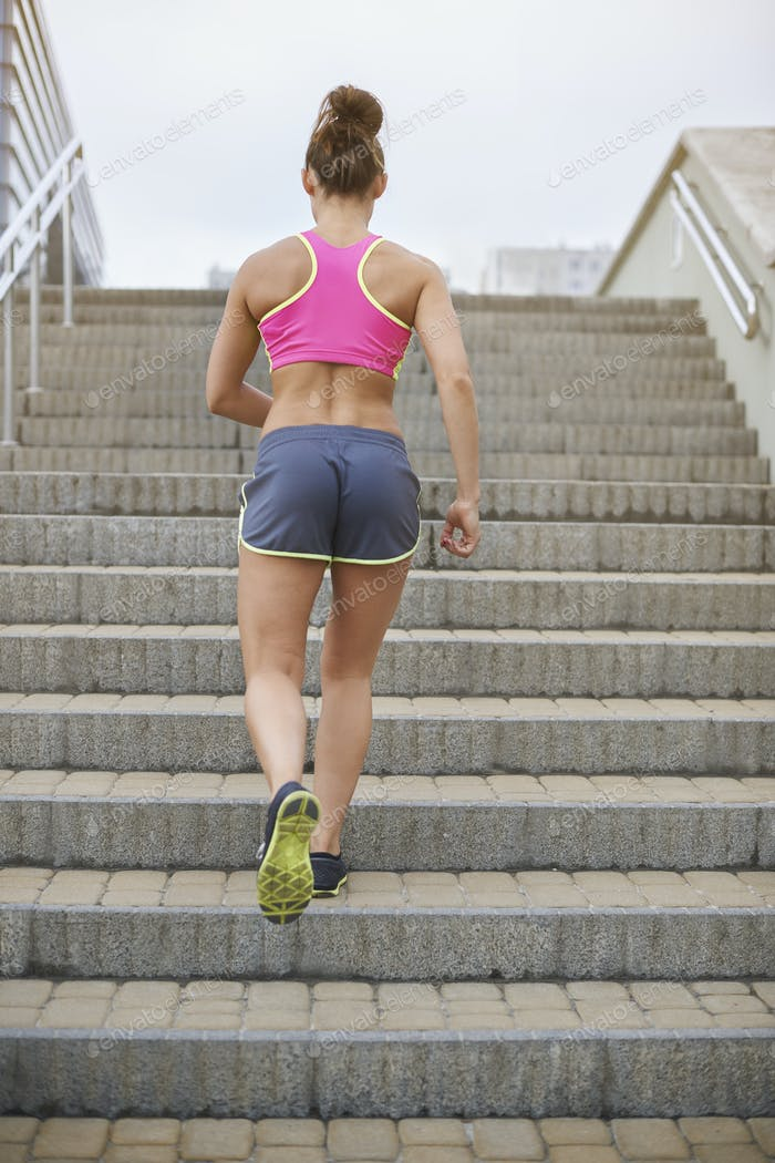 Athletic woman running up the steps