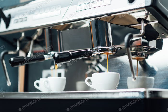 extraction of espresso from a bottomless portafilter in white cups