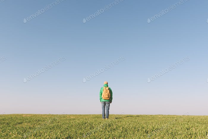 Tourist with backpack alone on summer field