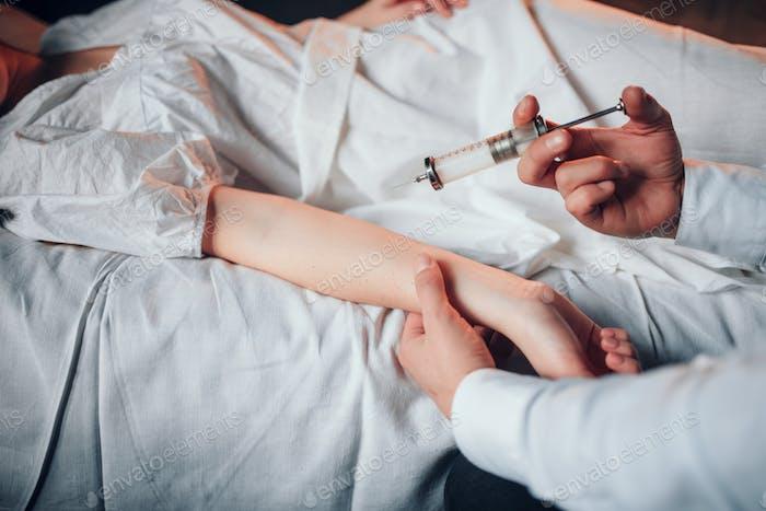 Männlicher Arzt macht Spritze Injektion für kranke Frau