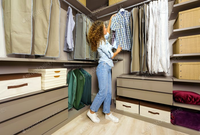 Young woman choosing clothes in a walk-in closet