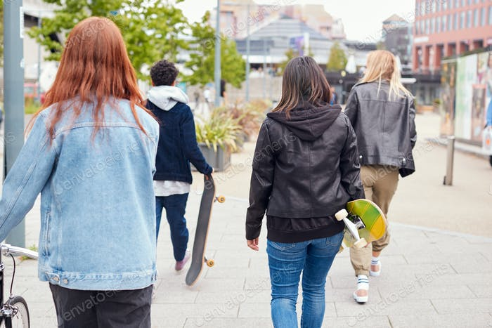 Rear View Of Female Friends With Skateboards And Bike Walking Through City Center