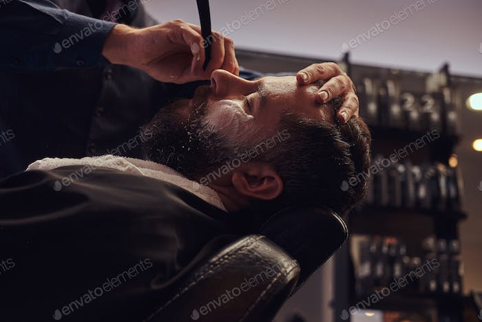 A handsome hipster bearded male sitting in an armchair in a barber shop