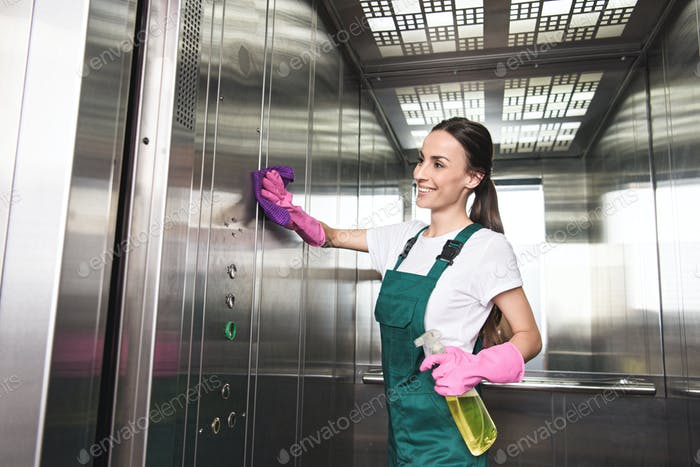 beautiful smiling young cleaner washing elevator with detergent and rag