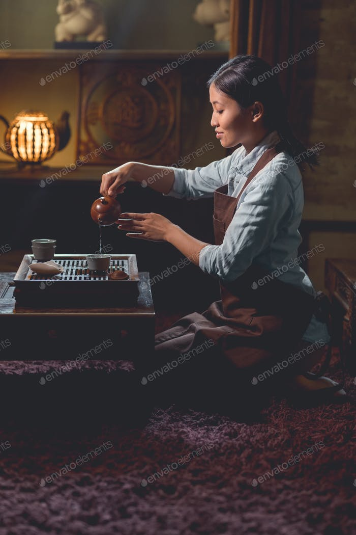 Young tea master pouring tea indoors