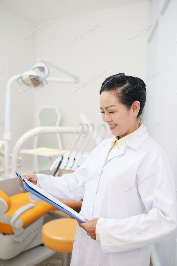 Cheerful ethnic dentist doctor with clipboard