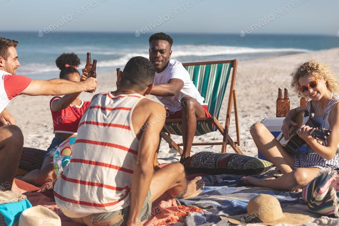 Front view of group of happy diverse friends toasting glasses of beer on the beach