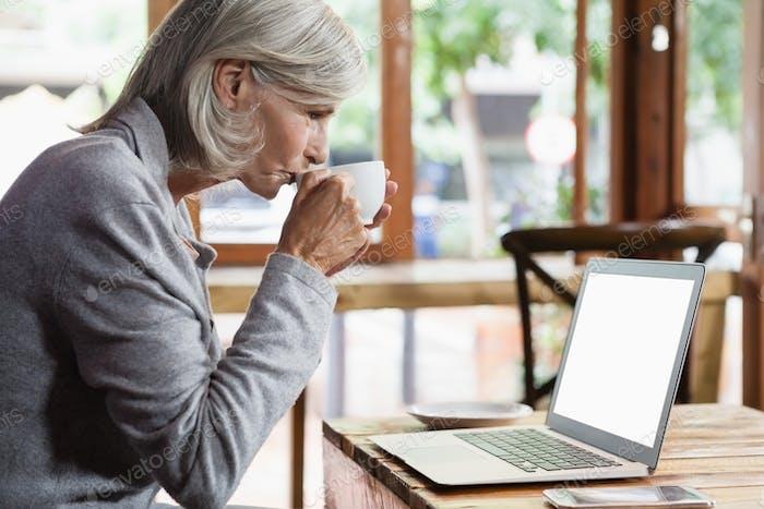 Seitenansicht der Senior Frau trinken Kaffee während der Verwendung von Laptop-Computer