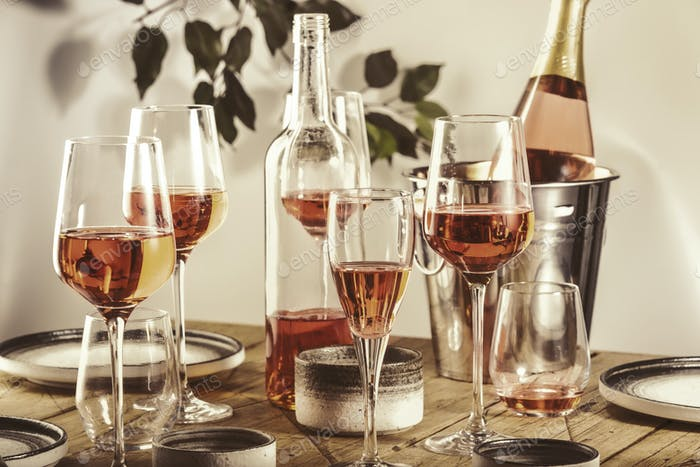 Rose wine glasses and bottles on table served for festive dinner party