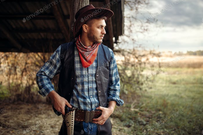 Brutal cowboy with his hand on revolver, wild west