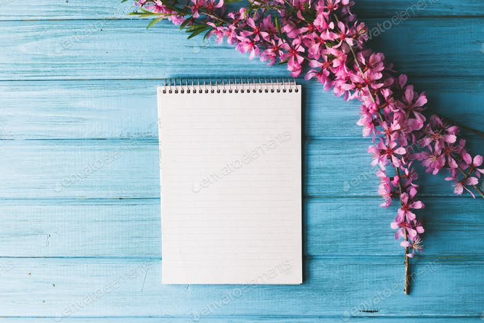 Blank notebook and wild flowers on blue wooden background. Concept flowers of spring,