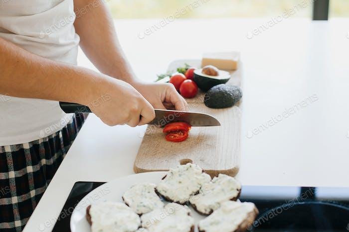 Person schneidet Tomatenscheibe für Sandwich