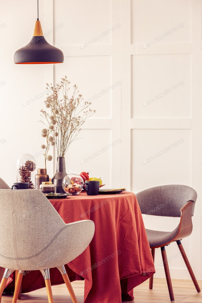 Stylish grey chairs at dining table covered with long tablecloth
