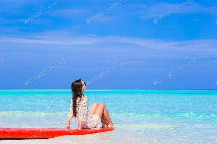 Junge Surferfrau am weißen Strand auf rotem Surfbrett
