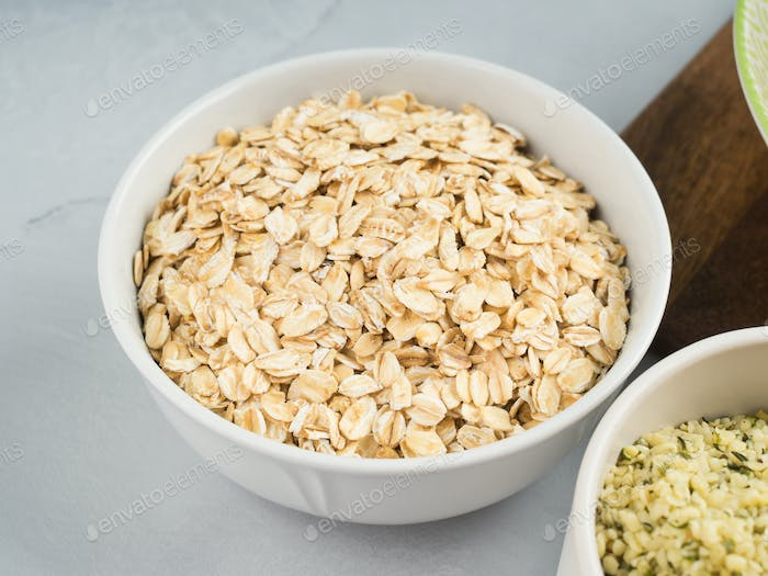 Oat flakes in bowl on gray background