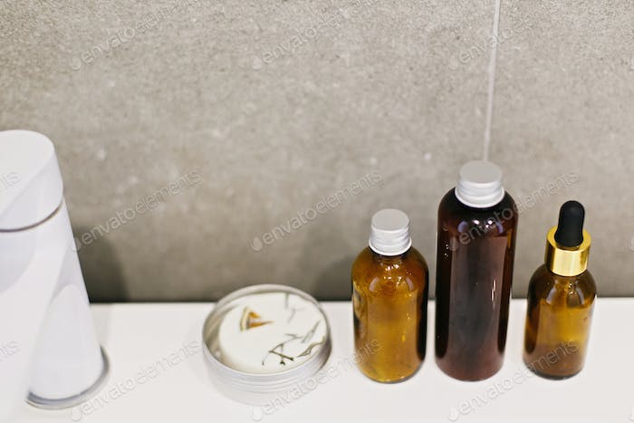 Ubtan for skin in glass bottle, cream in metal can, tonic,  conditioner on white sink