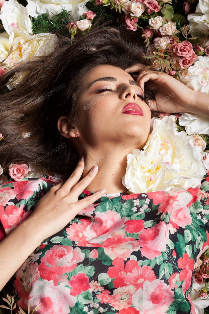 Sexy woman with closed eyes posing sensual while lying down on f