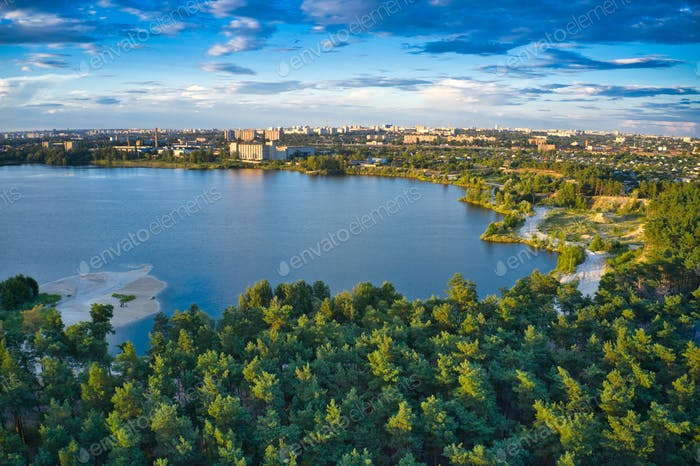 Lake near the forest and the city in the background