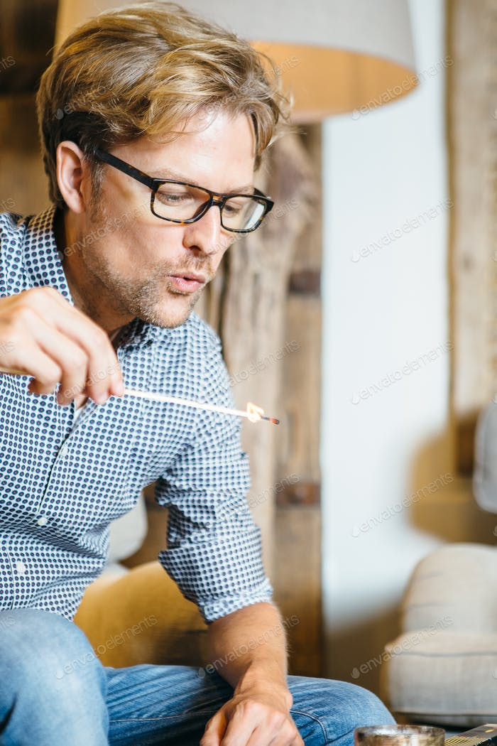 Young man blowing match