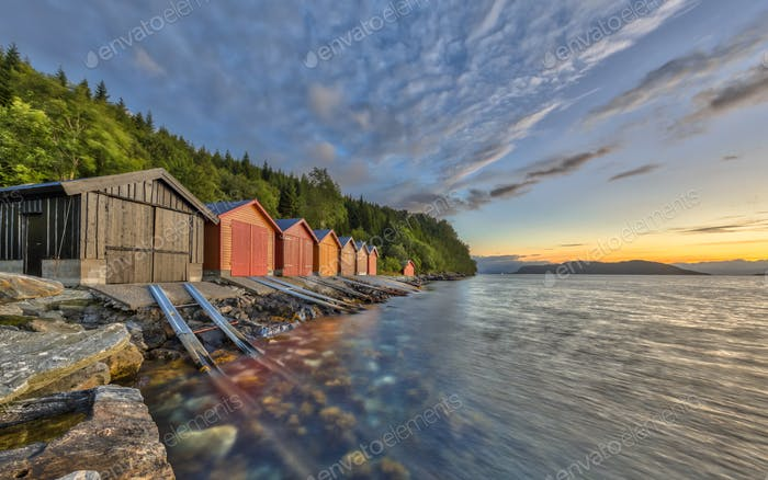Sonnenuntergang über norwegischem Fjord mit bunten Bootshäusen