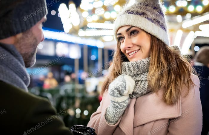 Sweet couple spend time together at the Christmas market in the evening