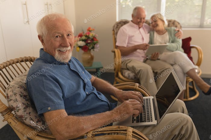 Side view of active senior man using laptop while senior couple using digital tablet at nursing home