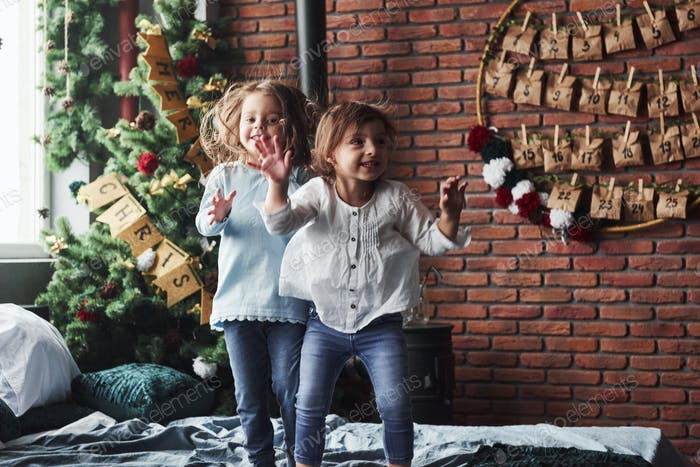 Cheerful kids having fun and jumping on the bed with decorative holiday background