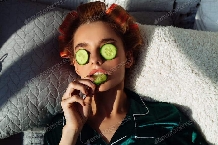 beauty female lying in bed with cucumber mask and hair curlers
