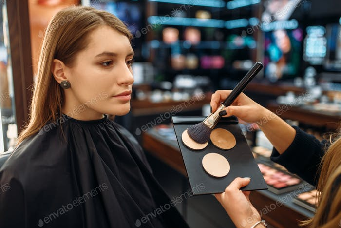 Visagiste applies powder, woman in makeup shop