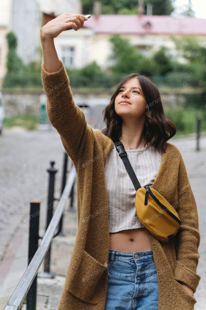 Young woman in casual fashionable outfit taking selfie while walking  in city street